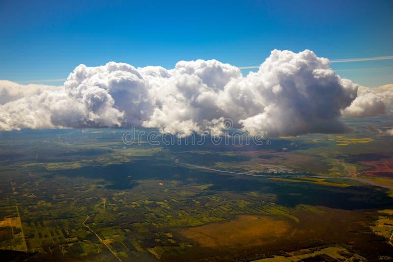 蓝天,云彩和地球可看见通过他们从平面窗口 库存图片