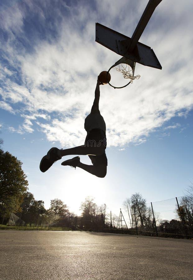 蓝球运动员灌篮剪影 免版税库存照片