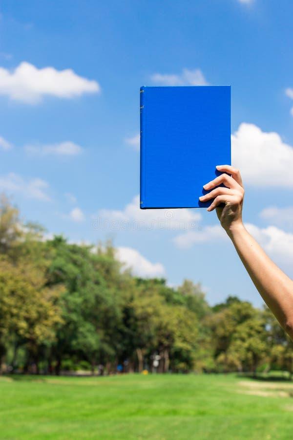 蓝皮书在手边 图库摄影