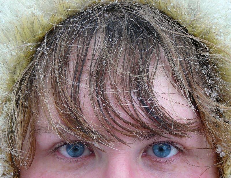 蓝眼睛在妇女之下的头发s雪 免版税库存图片