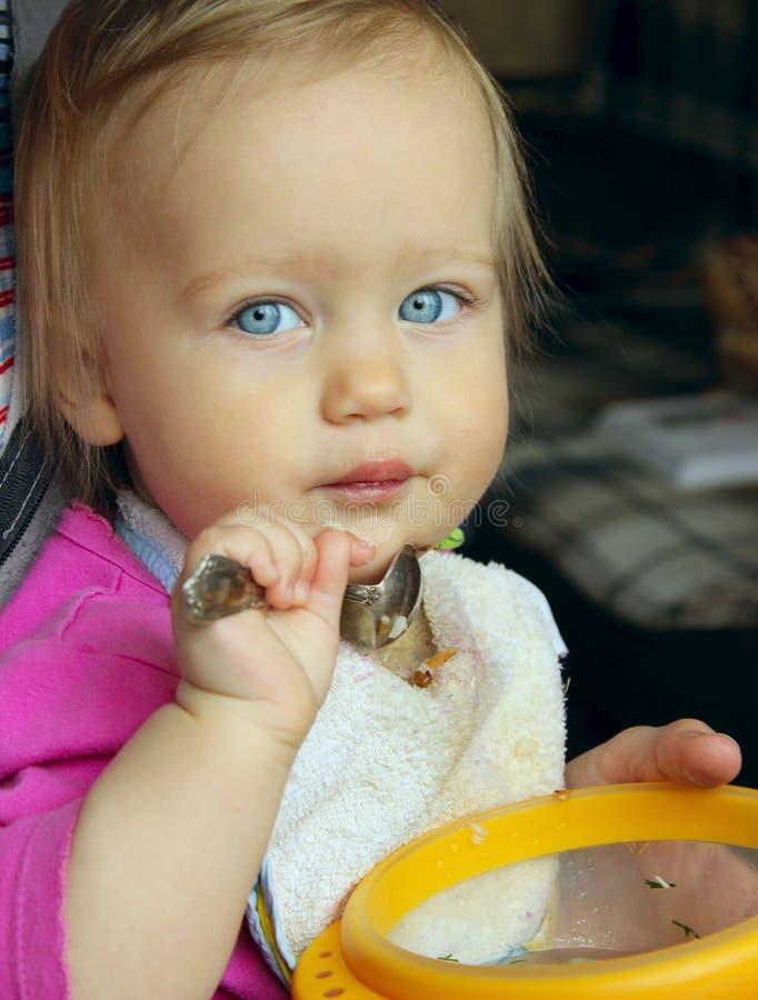 蓝眼睛女婴吃 库存图片