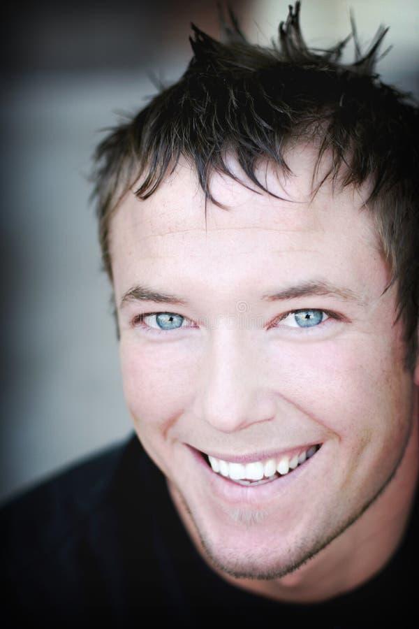 蓝眼睛的愉快的人年轻人 免版税库存照片