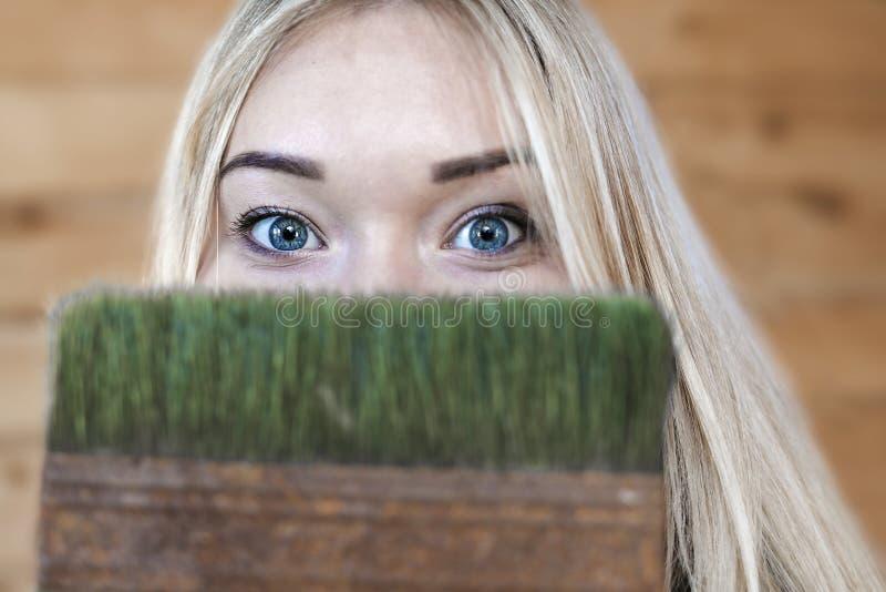 蓝眼睛的金发碧眼的女人打算做修理和决定开始以绘有绿色油漆的墙壁 库存照片