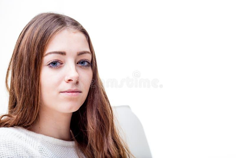 蓝眼睛长发女孩平静在她的沙发 图库摄影