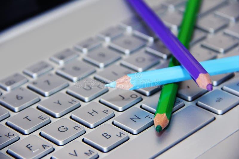 蓝绿色和紫色铅笔在一个银色键盘说谎 免版税库存照片