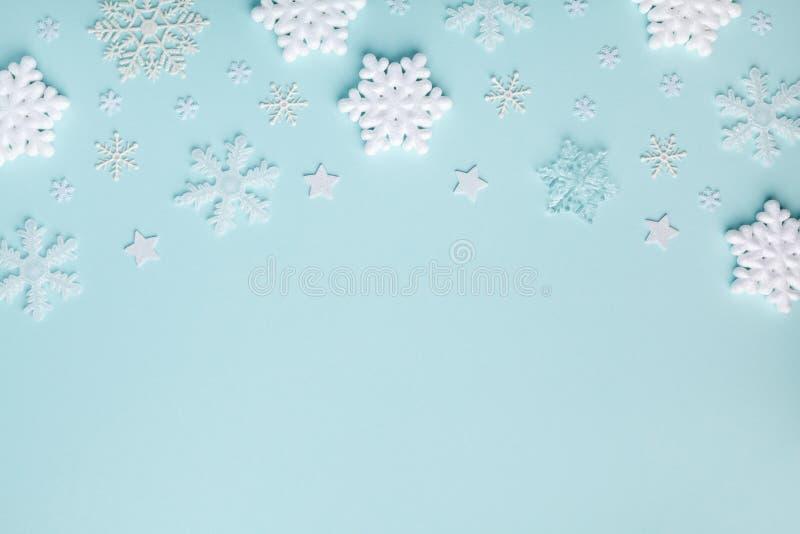 蓝绿色柔和背景上的白色装饰雪花 圣诞或新年贺卡顶视图 极简平铺 免版税库存图片