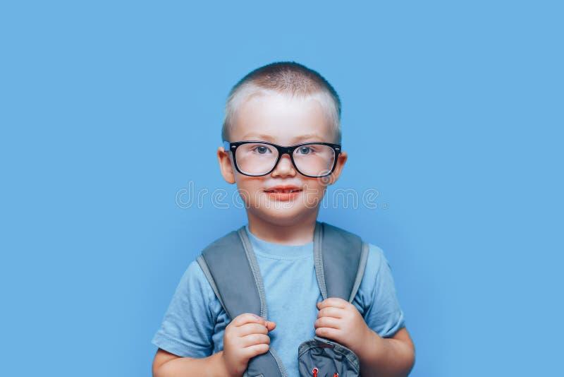 蓝背景的金发美男,背包不快乐,悲伤,孩子不想上学 回到学校 免版税库存照片