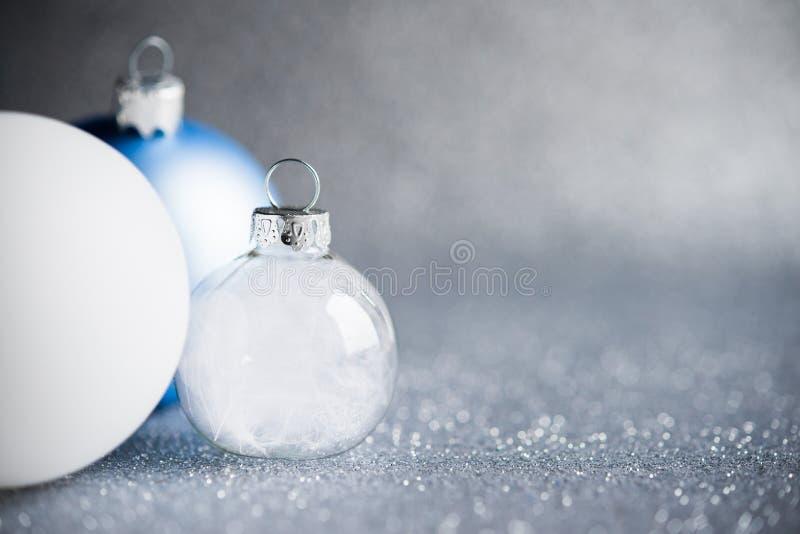 蓝色、银和白色xmas装饰品在闪烁假日背景 圣诞快乐看板卡 免版税库存图片