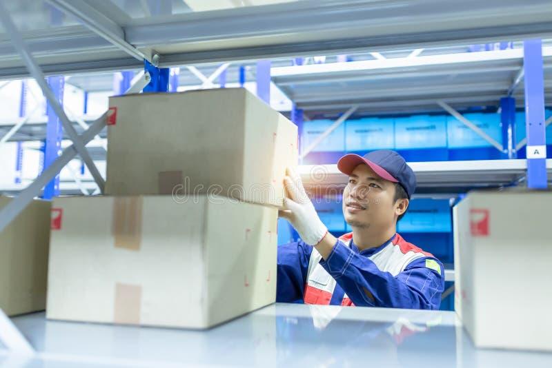 蓝色一致的工作的亚裔人交付职员在仓库保留物品,汽车机械师检查a的储蓄友好的工作者 图库摄影