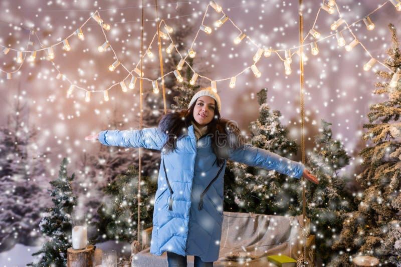 蓝色下来夹克欣喜的女孩由于降雪的站立的n 图库摄影