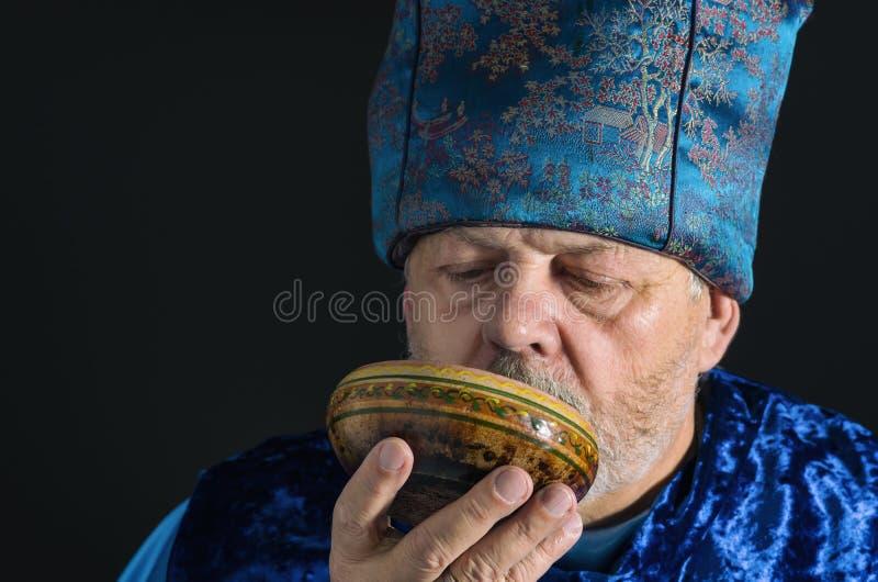 蓝色东方衣裳的喝茶的有胡子的老人画象  免版税库存图片