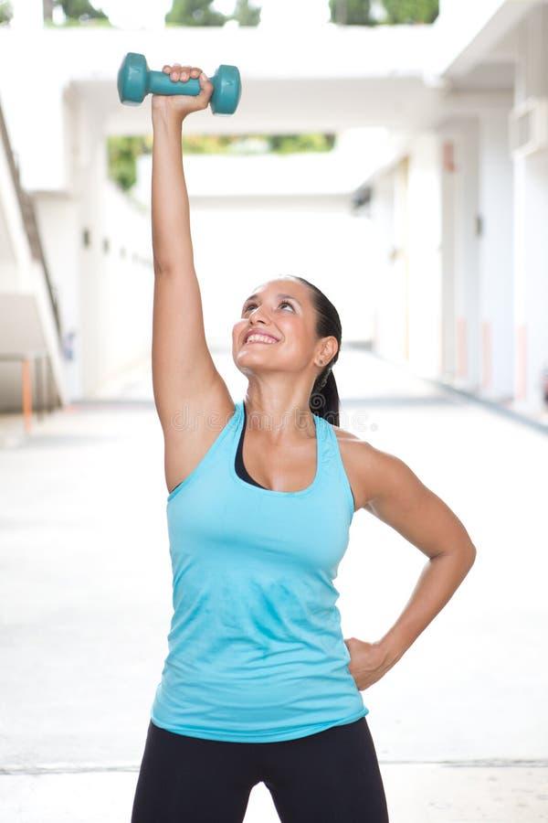 蓝色举的与右手,一个蓝色哑铃运动的西班牙妇女户外 库存图片