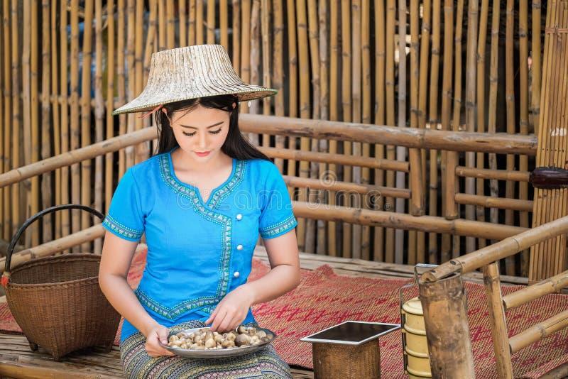 蓝色传统泰国样式礼服的女孩收集蘑菇送命令到顾客 库存照片