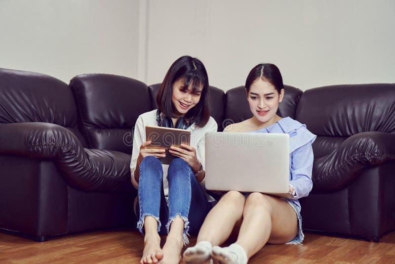 蓝色便服的亚裔女孩听到从黑耳机和用途膝上型计算机的音乐的 图库摄影