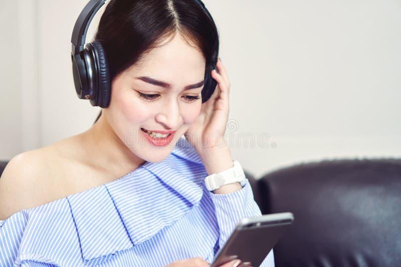 蓝色便服的亚裔女孩听到从黑耳机的音乐的 免版税库存照片