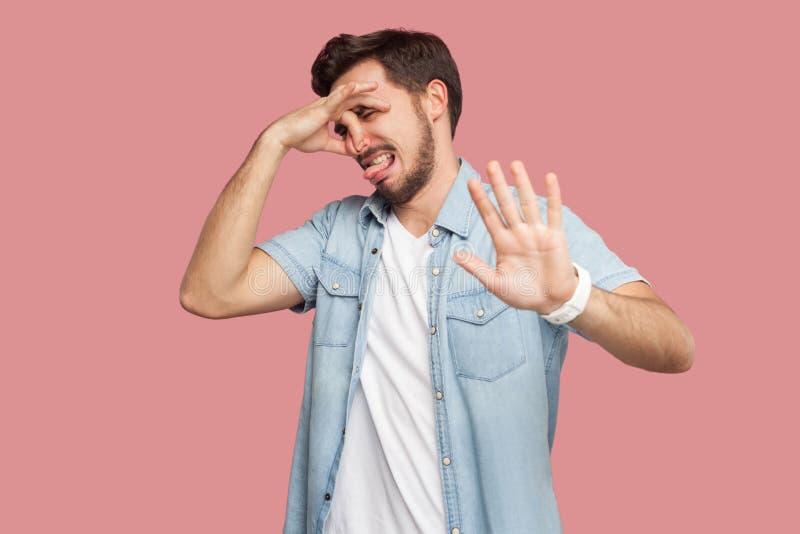 蓝色便装样式衬衣身分的,捏他的鼻子和显示中止的乏味或迷茫的英俊的有胡子的年轻人画象 免版税库存图片