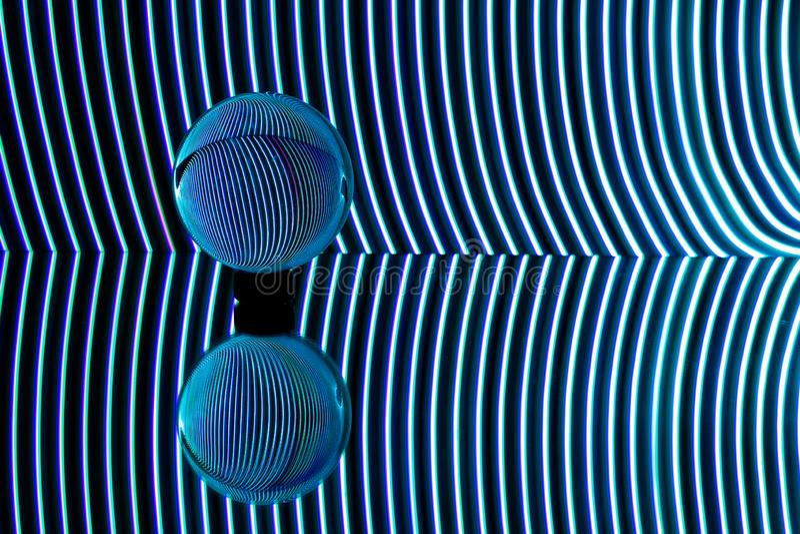 蓝色光在透明球形后弯曲了 轻的绘画摄影 免版税库存照片