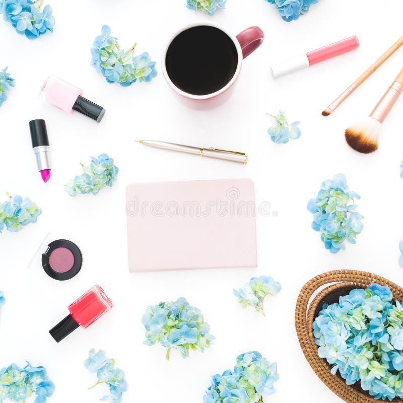 蓝色八仙花属的构成开花与女性化妆用品、日志和杯子在白色背景的咖啡 平的位置,顶视图 Fl 库存照片