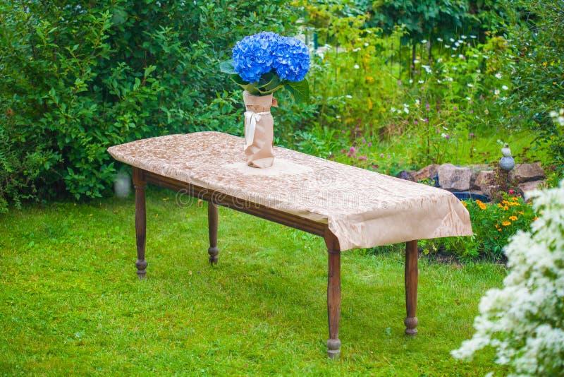 蓝色八仙花属花束在一个花瓶的在桌上 图库摄影