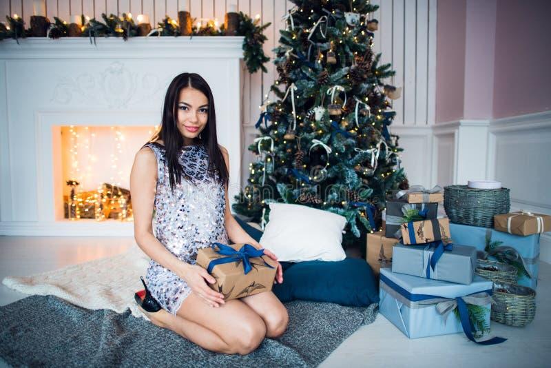 蓝色典雅的晚礼服的年轻美女坐自一个除夕的地板在圣诞树附近和礼物 库存图片