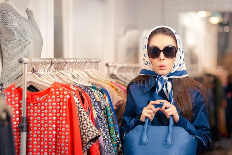 蓝色军用防水短大衣和太阳镜购物的好奇女孩 免版税图库摄影