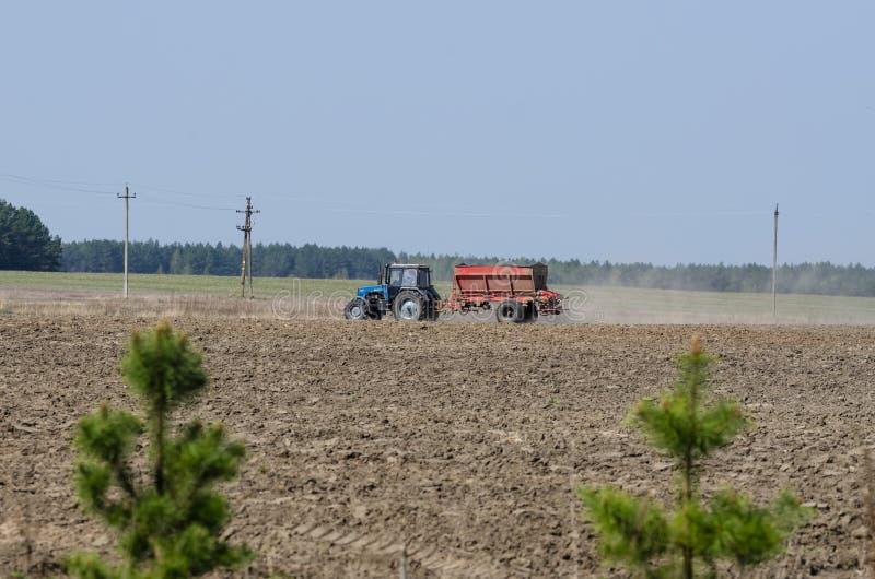 蓝色农用拖拉机施肥领域 图库摄影