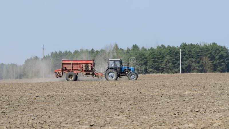 蓝色农用拖拉机施肥领域 免版税库存图片