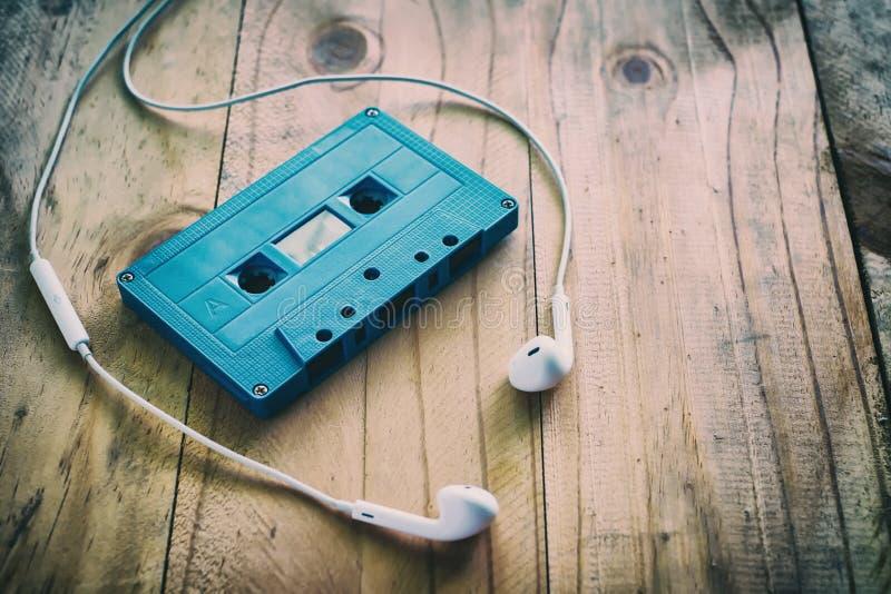 蓝色减速火箭的盒式磁带和白色耳机在木桌上 库存照片