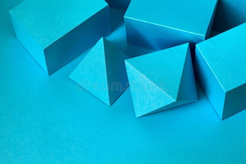 蓝色几何形象静物画构成 三维在蓝色的棱镜金字塔长方形立方体对象 库存照片