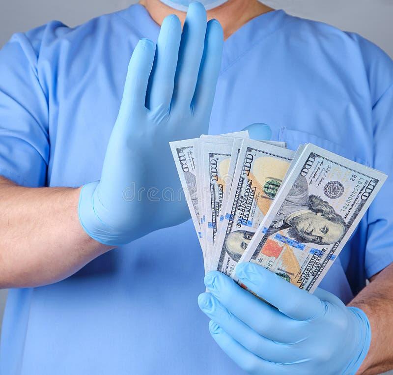 蓝色制服和全国数据交换网络手套的医生拿着很多纸币 库存照片
