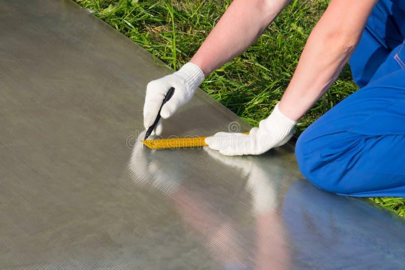 蓝色制服和手套的,标记工作者切除聚碳酸酯纤维黄色统治者板料线  库存照片
