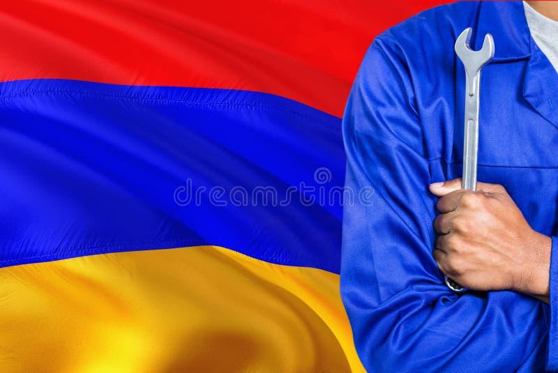 蓝色制服的亚美尼亚技工拿着板钳反对挥动亚美尼亚旗子背景 横渡的胳膊技术员 图库摄影