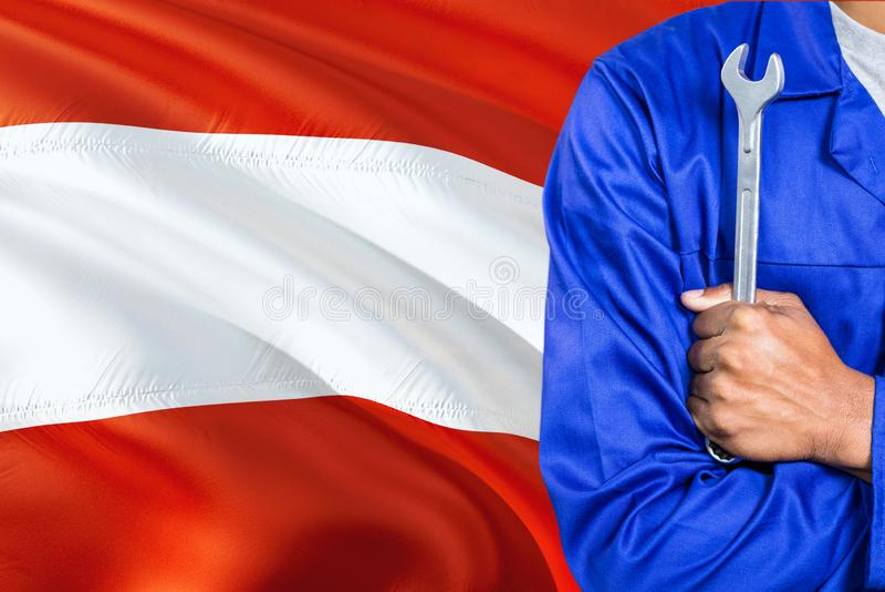 蓝色制服的奥地利技工拿着板钳反对挥动奥地利旗子背景 横渡的胳膊技术员 库存图片