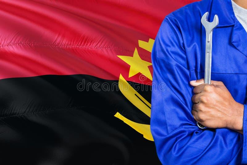 蓝色制服的安哥拉技工拿着板钳反对挥动安哥拉旗子背景 横渡的胳膊技术员 免版税图库摄影