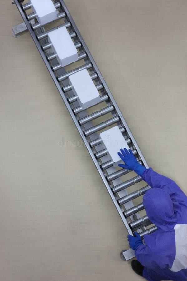 蓝色制服的工作者与在包装线的箱子一起使用 库存图片