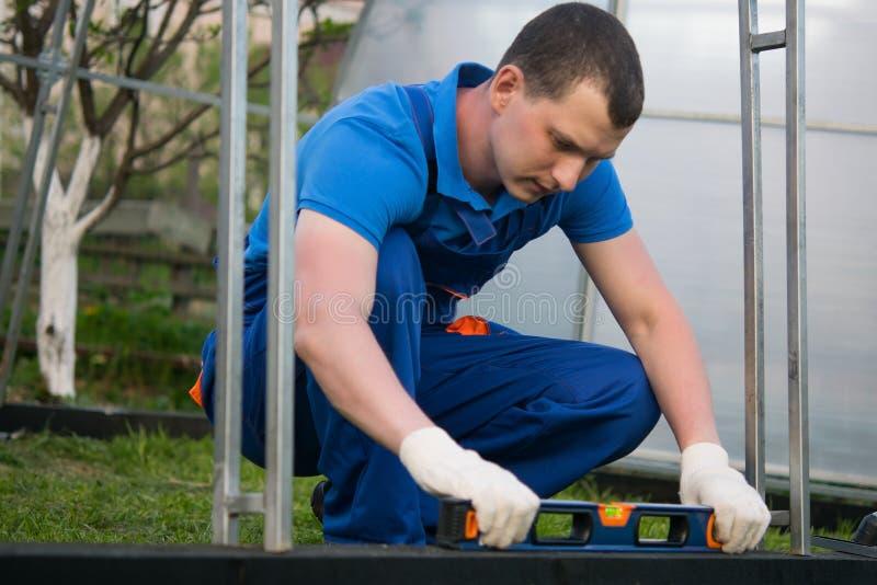 蓝色制服的工作者,在街道上,检查木基础温室,与专辑 免版税库存图片