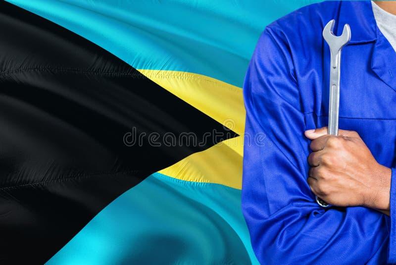 蓝色制服的巴哈马群岛的技工拿着板钳反对挥动巴哈马旗子背景 横渡的胳膊技术员 库存图片