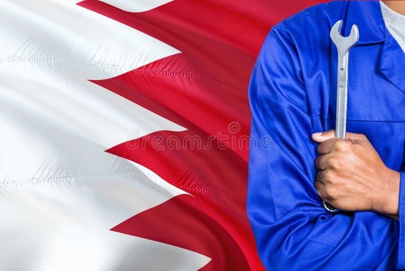 蓝色制服的巴林技工拿着板钳反对挥动巴林旗子背景 横渡的胳膊技术员 库存照片