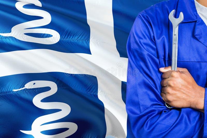 蓝色制服的技工拿着板钳反对挥动马提尼克岛旗子背景 横渡的胳膊技术员 免版税库存图片