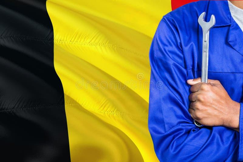 蓝色制服的比利时技工拿着板钳反对挥动比利时旗子背景 横渡的胳膊技术员 免版税库存照片