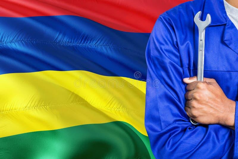 蓝色制服的毛里求斯技工拿着板钳反对挥动毛里求斯旗子背景 横渡的胳膊技术员 免版税库存图片