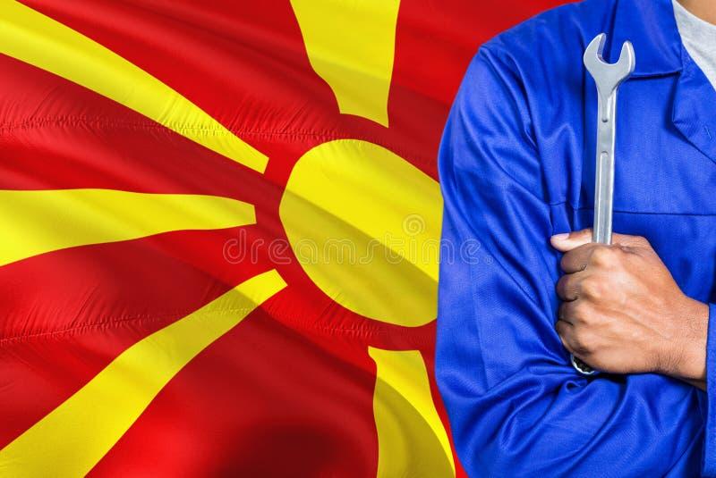 蓝色制服的马其顿技工拿着板钳反对挥动马其顿旗子背景 横渡的胳膊技术员 免版税库存图片