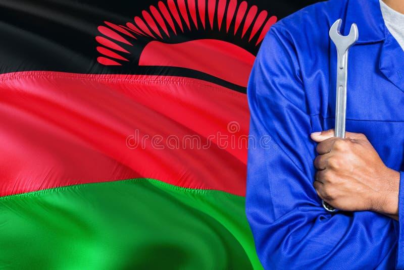 蓝色制服的马拉维技工拿着板钳反对挥动马拉维旗子背景 横渡的胳膊技术员 免版税库存照片