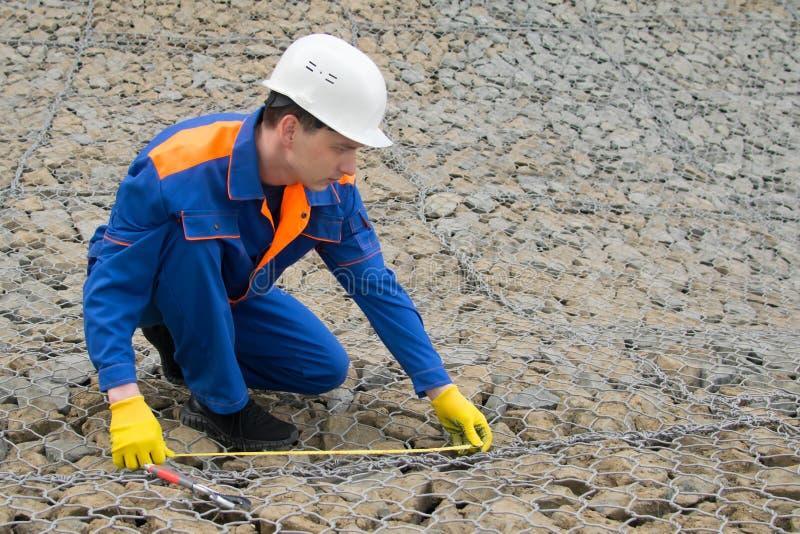蓝色制服的,用于河床的建筑的石头测量的磁带品种工作者,有的一个地方 库存照片