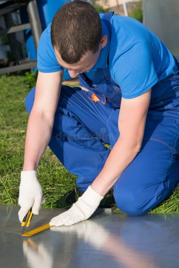 蓝色制服的,裁减工作者装饰板料屋顶的 库存照片