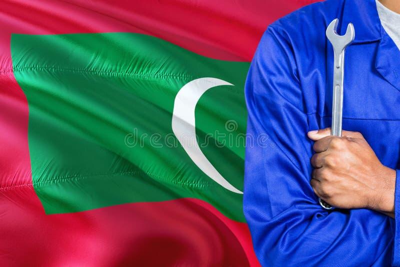 蓝色制服的Maldivan技工拿着板钳反对挥动马尔代夫旗子背景 横渡的胳膊技术员 免版税图库摄影