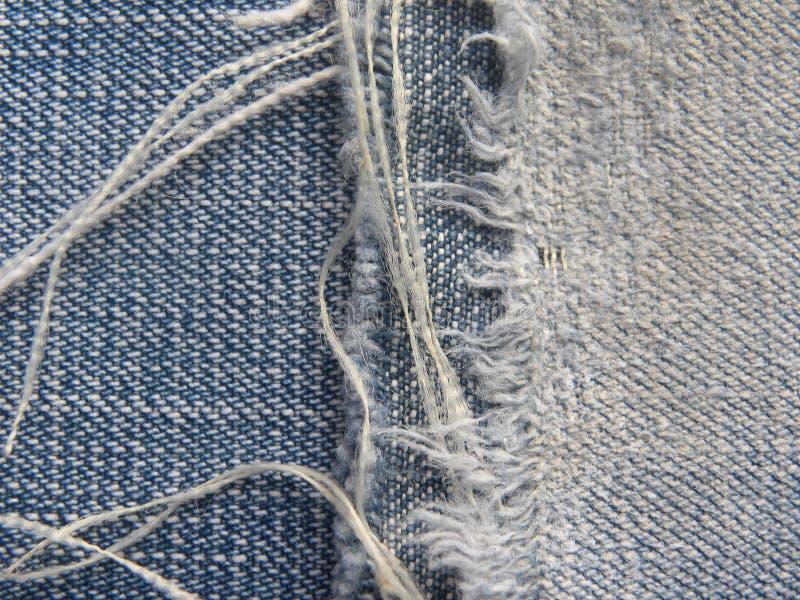 蓝色剥去了牛仔裤有螺纹背景 库存照片