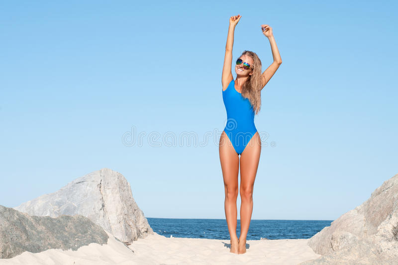 蓝色单件泳装的性感的被晒黑的妇女在热带海滩 免版税库存图片