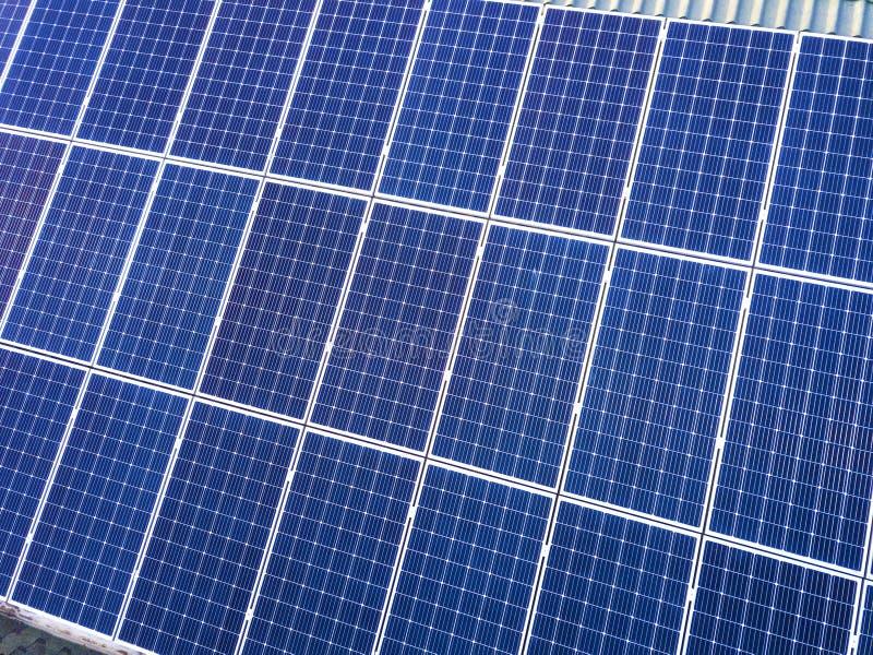 蓝色发光的太阳在大厦屋顶的照片流电盘区系统特写镜头表面  可更新的生态绿色发电 图库摄影