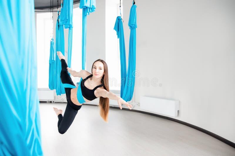 蓝色吊床的年轻美女体操运动员 空中飞行瑜伽在白色演播室 免版税库存图片